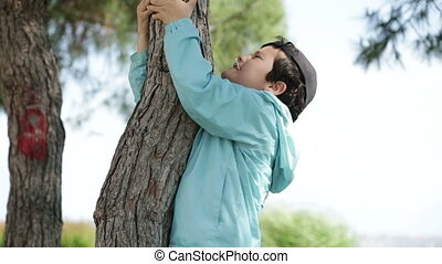 Little boy trying to climb the tree