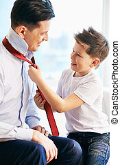 Getting dressed - Photo of happy boy tying necktie of his...