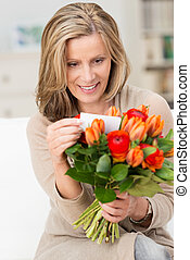 Excited woman reading the note on a bouquet