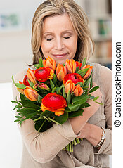 Woman hugging a bunch of fresh flowers