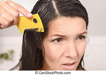 Woman combing out lice in her hair with a lice comb...