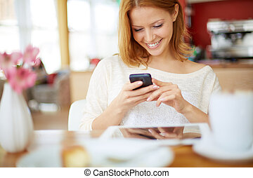 Free time - Image of young female reading sms on the phone...
