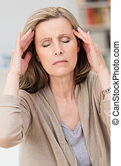 Middle-aged woman with a migraine headache sitting with her...