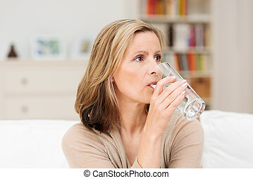 Thirsty woman drinking a glass of cold water