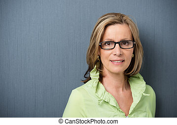 Elegant middle-aged woman in glasses looking directly at the...