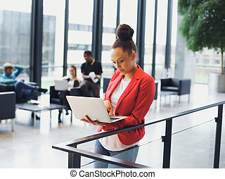 Young african woman using laptop in office