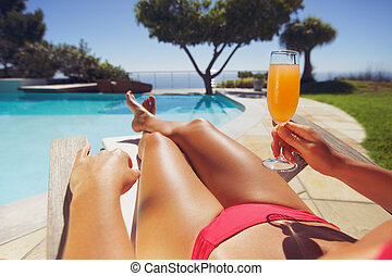 Woman lying on deck chair with fruit juice