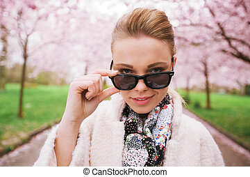Beautiful female looking through sunglasses at spring park -...