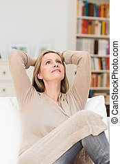 Pretty middle-aged woman sitting daydreaming on a sofa in...