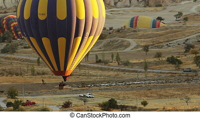 Big colorful hot air balloon flying over valleys in Goreme, Cappadocia, Turkey.