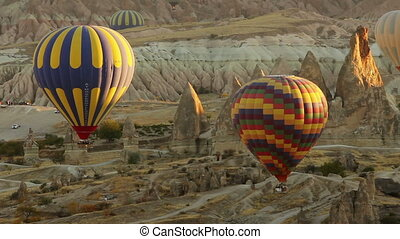 Colorful hot air balloons flying over valleys in Goreme,...