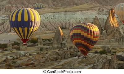 Timelapse of colorful hot air balloons flying over valleys...
