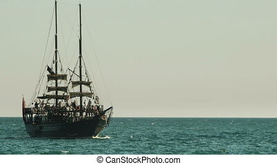 Tourists sailing on an old style wooden ship in Mediterranean sea in Antalya, Turkey