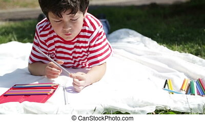 Child drawing on the grass - Child painting in the park