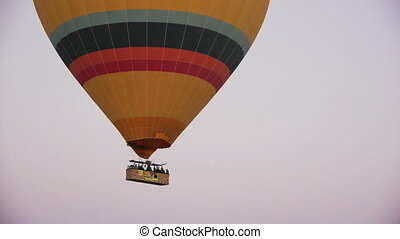 Big colorful hot air balloon flying over valleys in Goreme,...