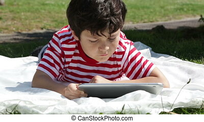 Child using digital tablet in the park