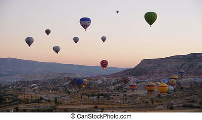 Lots of hot air balloons flying over valleys in Goreme,...