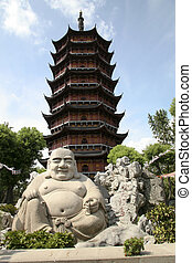 Smiling buddha statue in front of pagoda in Suzhou China