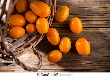 Kumquat - Kumquat berries on wooden background Citrus fruit...