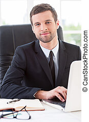 Confident and successful businessman. Handsome young man in formalwear working on laptop and smiling while sitting at his working place