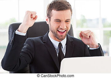 I did it! Happy young man in formalwear looking at computer monitor and gesturing while sitting at his working place