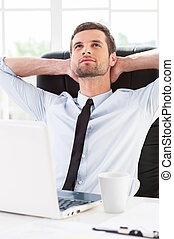 Day dreaming in office. Handsome young man in shirt and tie holding hands behind head and smiling while sitting at his working place