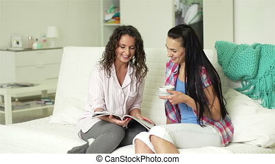 Visiting Friend - Two girls sitting on sofa having friendly...