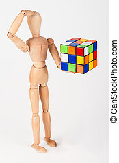 Confused wood mannequin hold cube puzzle confused before solving it