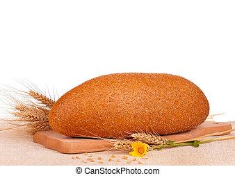 Fresh brad - Fresh bread with bran on a cutting board on...