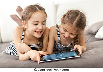 portrait of two smiling girls lying on couch and using...