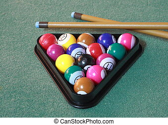 Pool balls on green cloth in triangle with cues