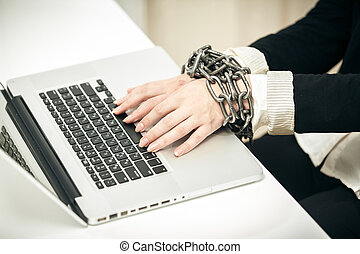 photo of female hand chained up to laptop - Closeup photo of...