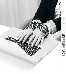 closeup photo of woman locked to laptop by chain - Black and...