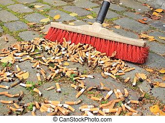 Sweeping a lot of cigarette butts from stone road