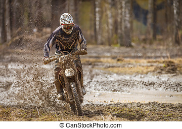 Motocross Race - Motocross driver on wet and muddy terrain...