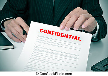 confidential - a man wearing a suit showing a document with...