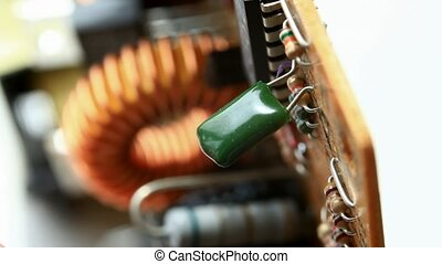 Hand pulling out condenser - Macro of hand unsoldering and...