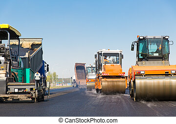Road works - Road rollers, tracked paver and truck during...