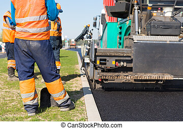 Road works - Tracked paver machine and construction workers...