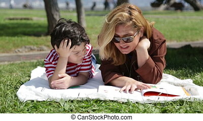Mother reading to son  in the park
