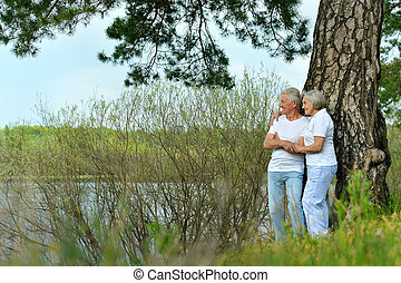 Happy senior couple standing in summer near lake