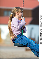 Girl on zip line while in mid-air. Taken on a sunny day.
