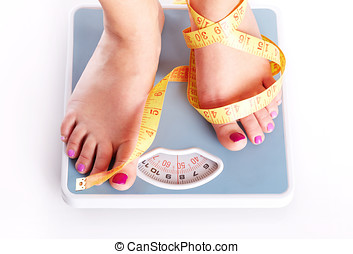 A pair of female feet standing on a bathroom scale and tape...