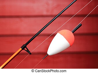 Red and white bobber on a fishing rod