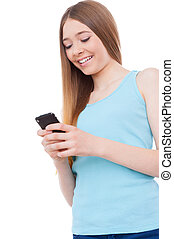 Teenage typing message. Cheerful teenage girl holding mobile...