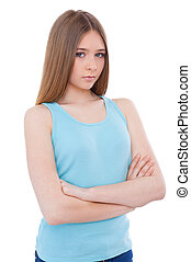 Difficult age. Sad young teenage girl keeping arms crossed...