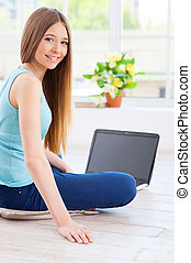 Spending time at home Cheerful teenage girl using computer...