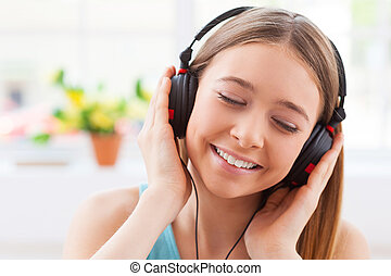 Day dreaming with her favorite music. Cheerful teenage girl in headphones listening to the music and keeping eyes closed while sitting in her apartment