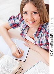 Smart and confident schoolgirl. Top view of cheerful teenage...