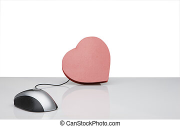 Dating online - computer mouse connected to red heart